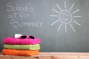 Blackboard with a sun and sign reading school's out for summer. Towels, sunglasses, and lotion are on a bench.